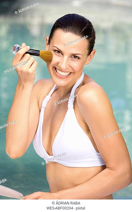 Young woman applying blusher with brush, portrait