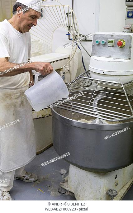 Baker pouring water in an industrial kneading machine