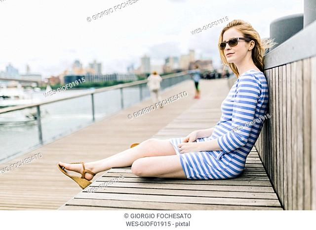 Young woman sitting at pier