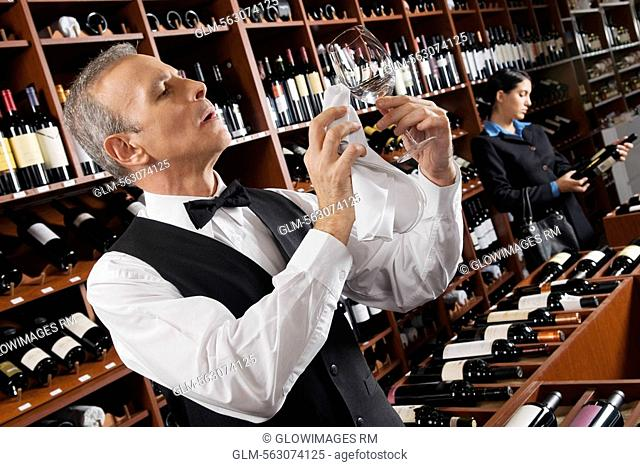 Waiter polishing a wine glass and a businesswoman choosing a bottle in a bar