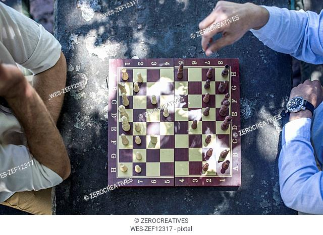 Top view of two men playing game of chess