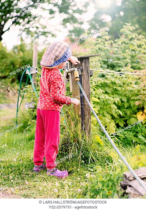 Side view of young child standing in garden helping with the watering hose