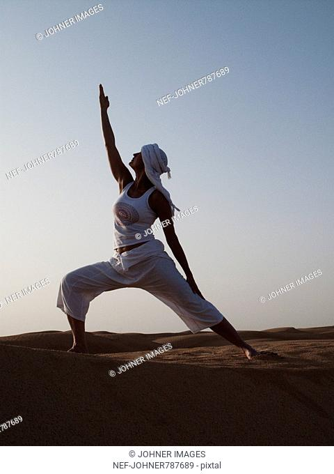Woman performing yoga in the desert, Tunisia