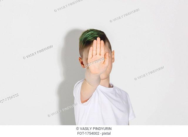 Boy showing stop sign while standing against white background