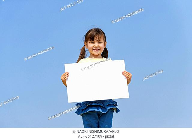 Young Japanese girl holding whiteboard and blue sky