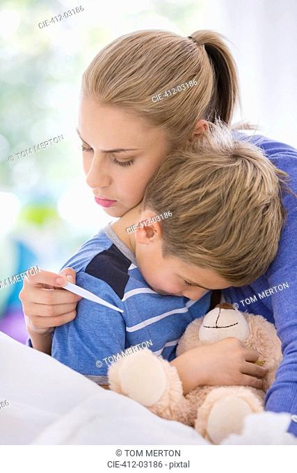 Mother hugging sick son in bed