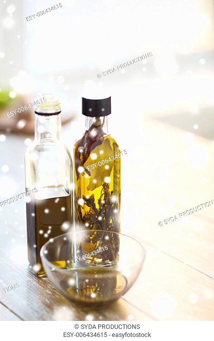 cooking and food concept - close up of two olive oil bottles and glass bowl on wooden table at home kitchen