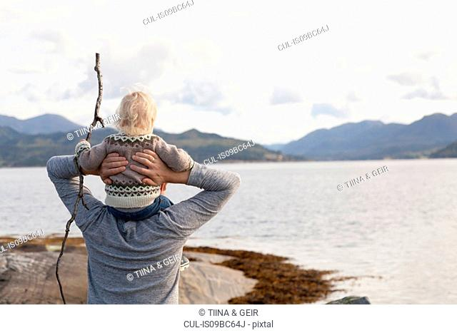 Man and son looking out at fjord, Aure, More og Romsdal, Norway