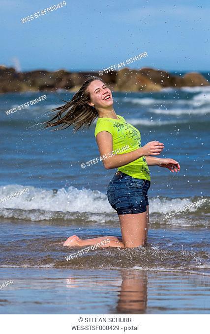 Female teenager having fun at waterside of the beach