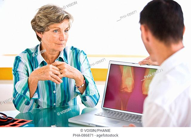 Doctor discussing arthosis x-ray of knees with a patient