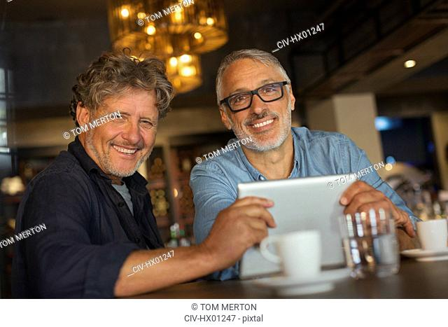 Portrait smiling men using digital tablet and drinking coffee at restaurant table