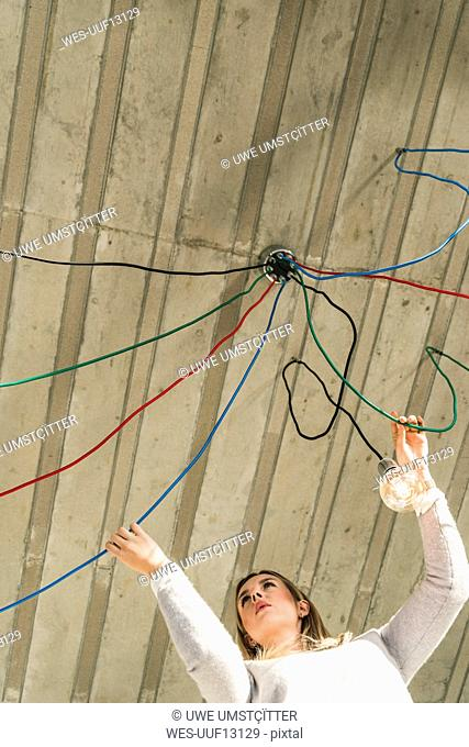 Young businesswoman in office examining cables at light bulb