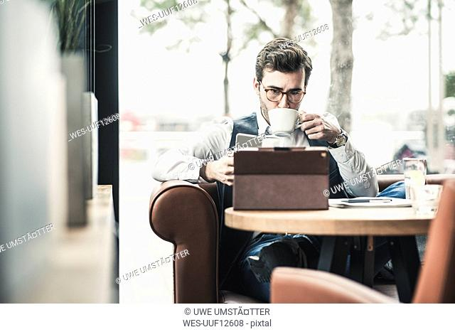 Young man working in a cafe using tablet and drinking coffee