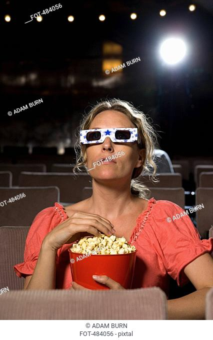 A woman sitting in a movie theater wearing 3-D glasses and eating popcorn