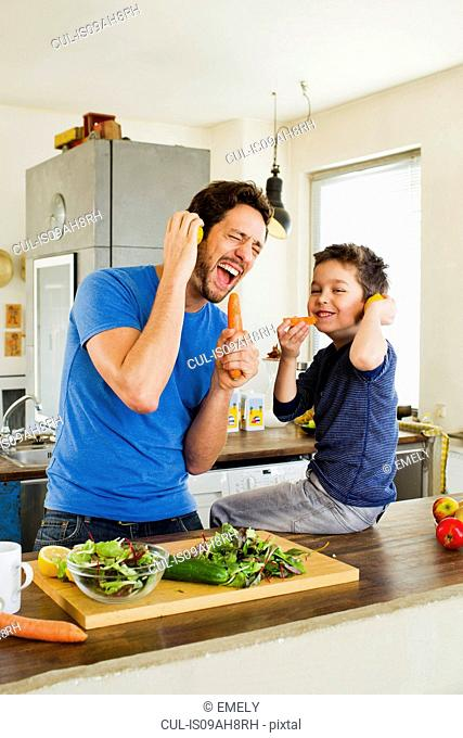 Father and young son singing into carrot microphones