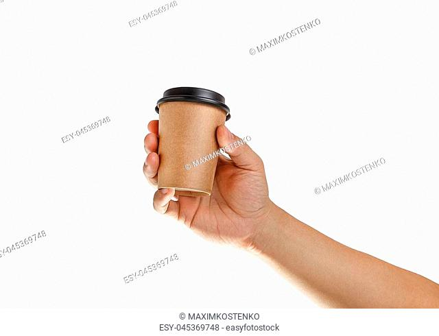 Man's hand holding craft empty paper coffee cup with a black plastic cap isolated on a white background