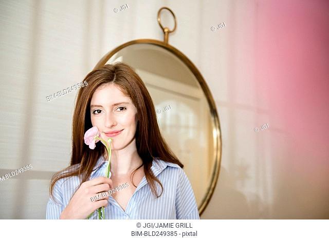 Portrait of Caucasian woman holding flower near mirror