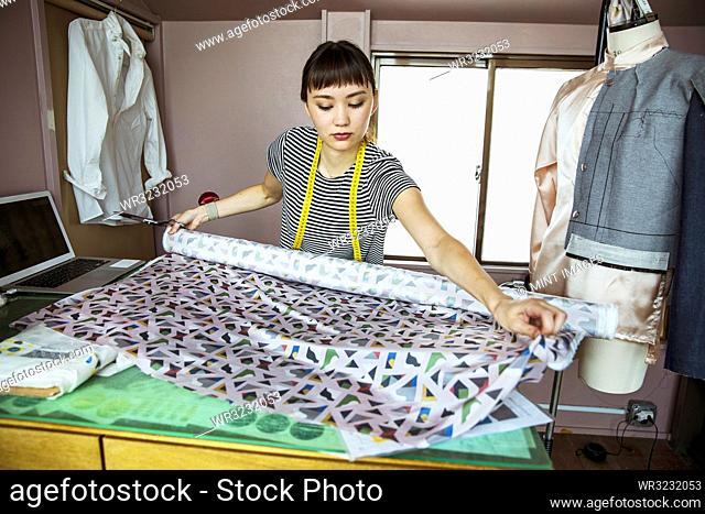 Japanese female fashion designer working in her studio, measuring fabric
