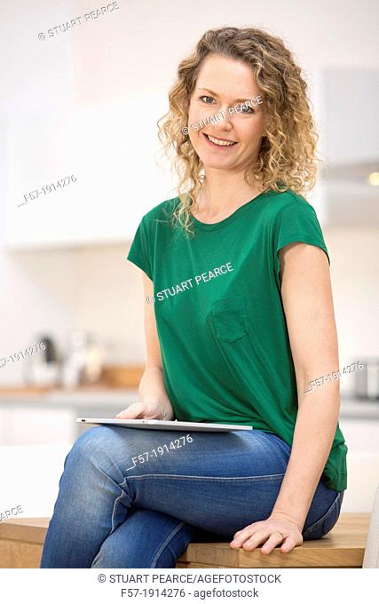 Independent young woman working at home on a tablet computer
