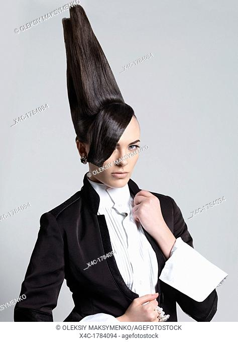 Artistic portrait of a woman with a creative tall vertical hairstyle