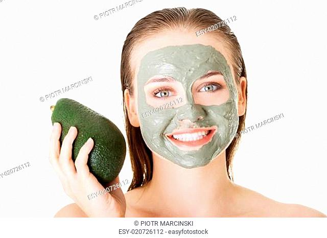 Beautiful woman with green avocado clay facial mask