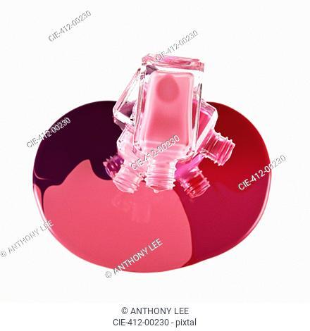 Multicolor fingernail polish spilling from stacked bottles