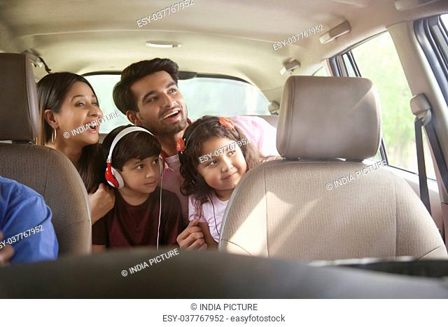 Happy family sitting in back seat looking out of car window