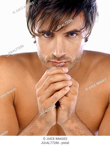 Man with bare chest resting head on hands