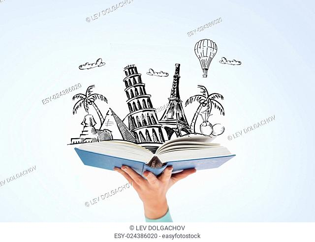 literature, travel and education concept - close up of woman hand holding open blue book with doodles