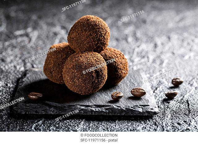 Truffle pralines with coffee beans on a black stone