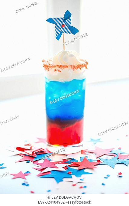american independence day, celebration, patriotism and holidays concept - glass of cocklatil drink with whipped cream and pinwheel decoration on american...