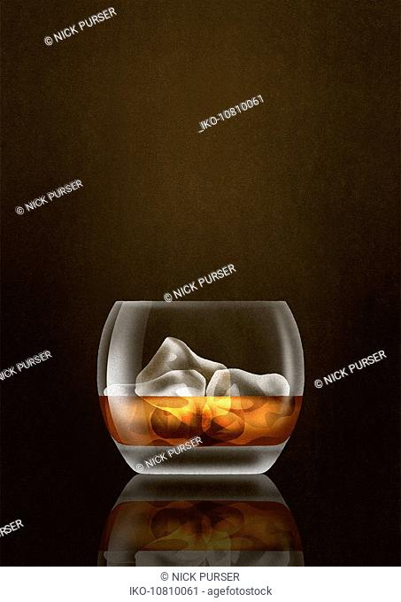 Close up of whisky and ice cubes in tumbler glass
