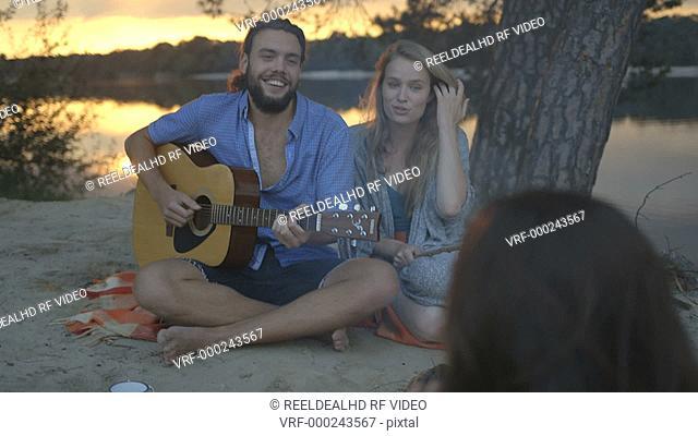 Friends enjoying music and smoking fish near campfire