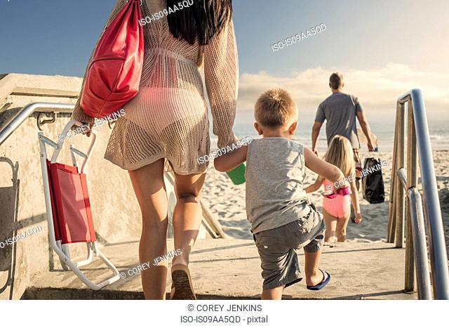 Young woman arriving at beach with son
