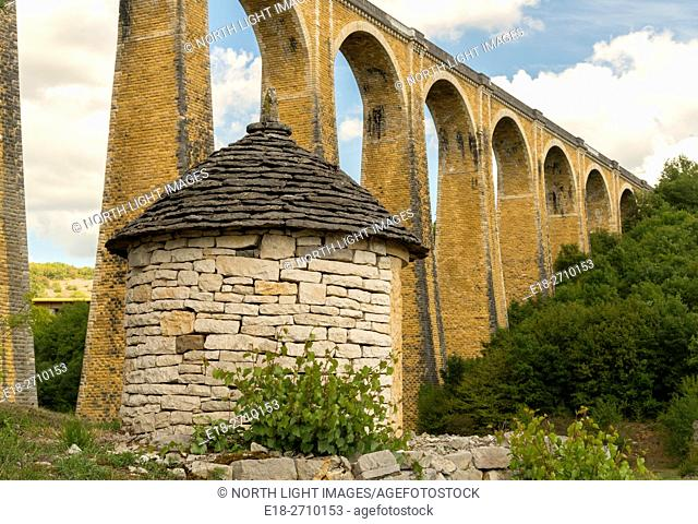 France, Midi-Pyrénées, Lot, Souillac. High arching, stone supports of railway bridge over deep valley. Old stone shed in the foreground