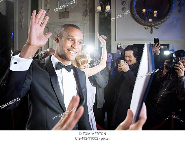 Well dressed male celebrity waving to fans and paparazzi at red carpet event