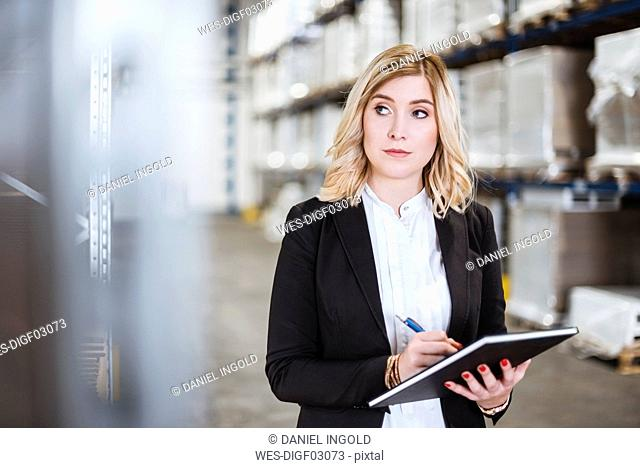 Blond businesswoman standing in storehouse, writing in notebook