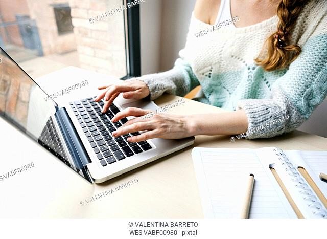 Woman working with laptop, partial view
