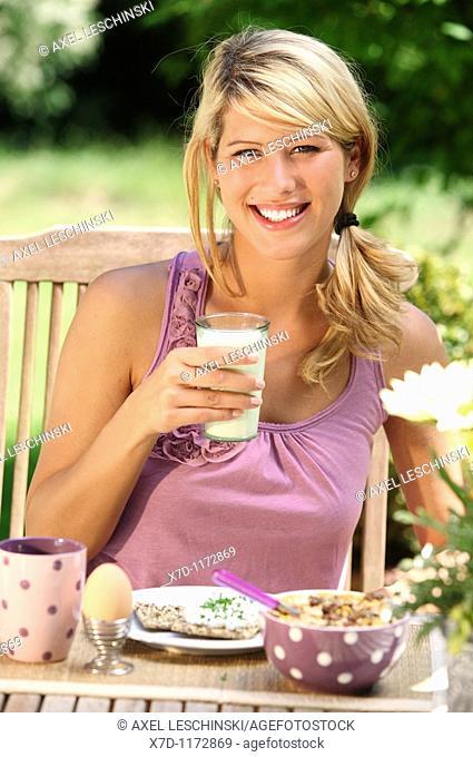 portrait of woman having breakfast in garden drinking milk