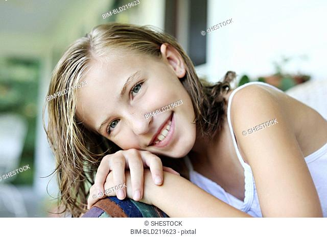 Close up of smiling girl leaning in armchair