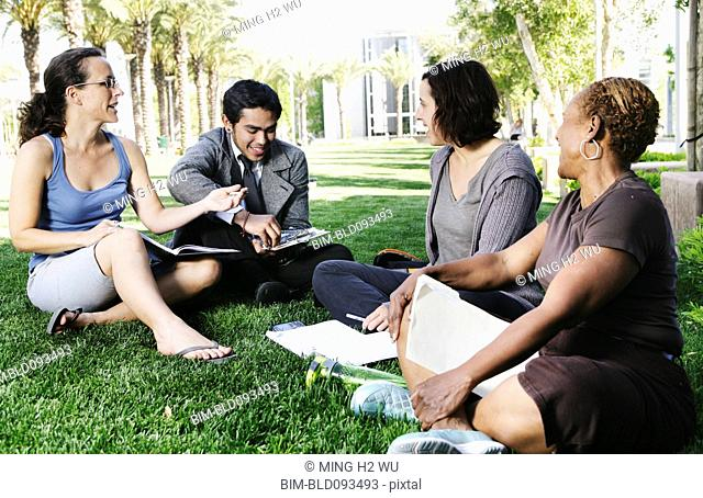Adult students studying together in park