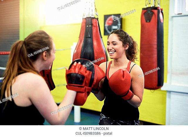 Female boxer training, punching teammates punch mitt