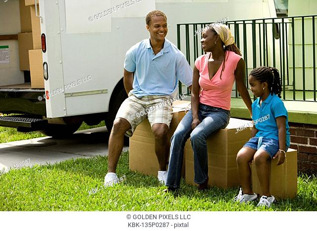 Family sitting on boxes outside house