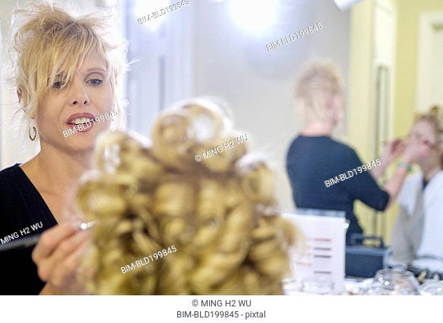 Caucasian woman having her hair and makeup done
