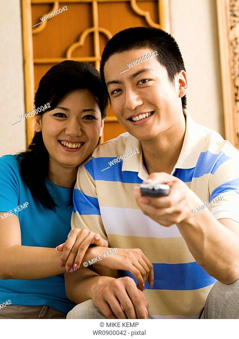 Couple sitting on sofa watching television smiling