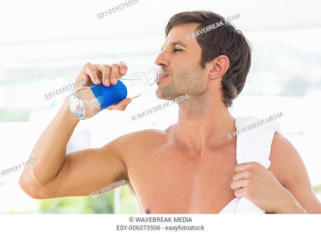 Shirtless man with towel drinking water