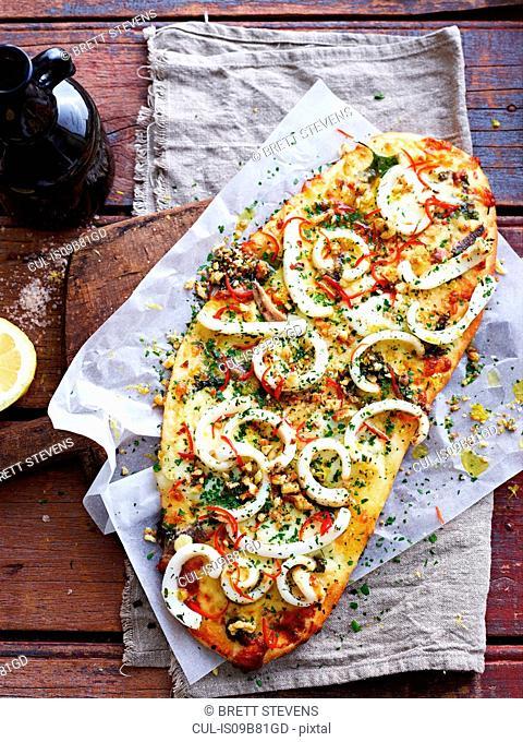 Squid aglio olio pizza on serving board, overhead view