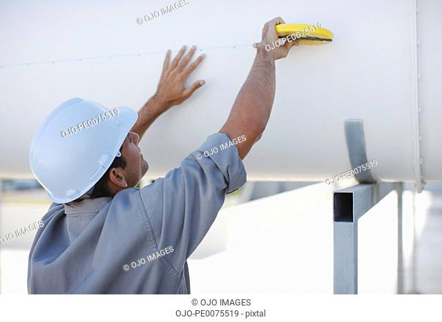 Worker measuring large pipe outdoors