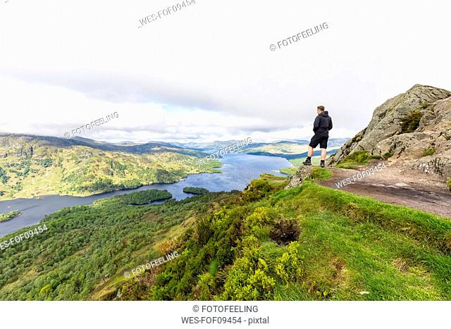 UK, Scotland, Highland, Trossachs, tourist looking from mountain Ben A'an to Loch Katrine