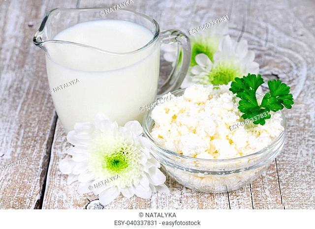 Milk and cottage cheese on old wooden board